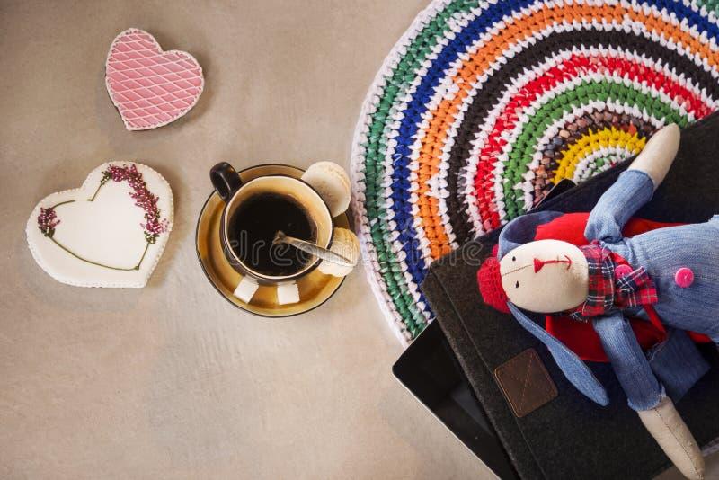软的玩具兔子,膝上型计算机关闭了,地毯、一杯咖啡和姜饼曲奇饼 库存照片