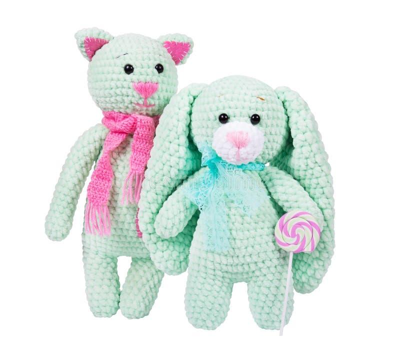 软的被编织的玩具和棒棒糖在白色背景 与桃红色围巾的豪华的钩针编织的猫 免版税图库摄影