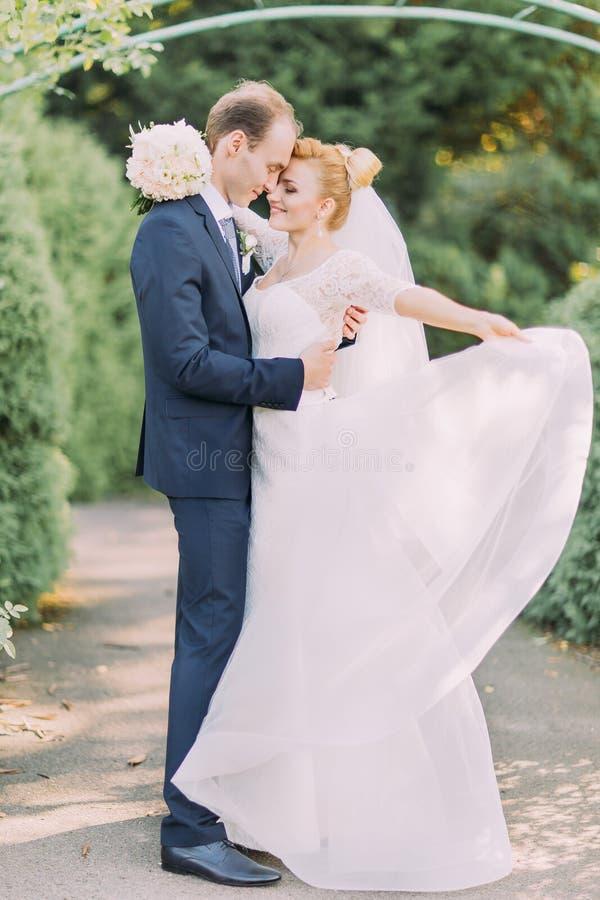 软软地拥抱在公园的新郎和新娘 花新娘婚礼花束在手上 库存照片