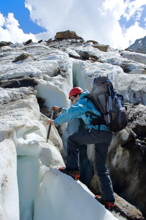 轴背包徒步旅行者上升的冰川冰妇女 免版税图库摄影