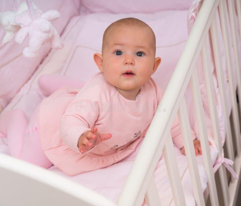 轻便小床的戒备好奇矮小的女婴 免版税图库摄影