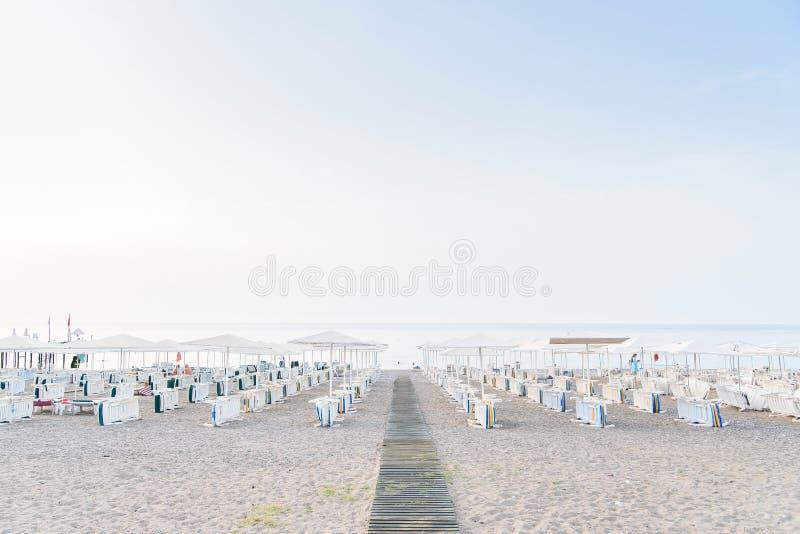 轻便折叠躺椅田园诗场面在一个干净的海滩的一把伞下在热的下午太阳 库存照片