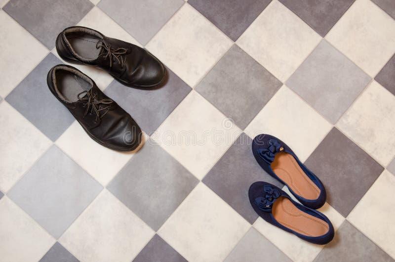 轻和舒适的蓝色妇女的鞋子和人的鞋子在黑白方格的地板上 免版税库存照片