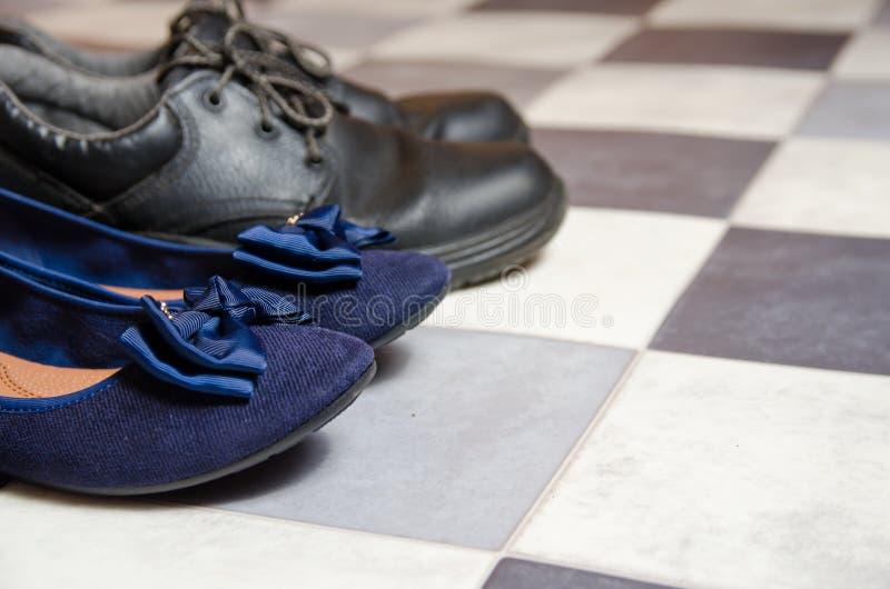 轻和舒适的蓝色妇女的鞋子和人的鞋子在黑白方格的地板上 库存图片
