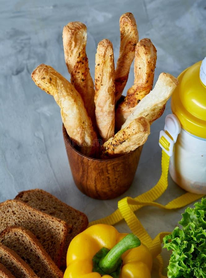轻快早餐用新鲜的酥皮点心、菜、绿叶和饮料在光构造了背景,顶视图, 免版税库存图片