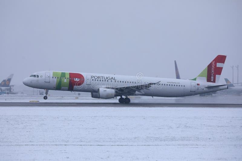 轻拍乘出租车在跑道的葡萄牙航空飞机在慕尼黑国际机场,德国,与雪的冬时 库存图片