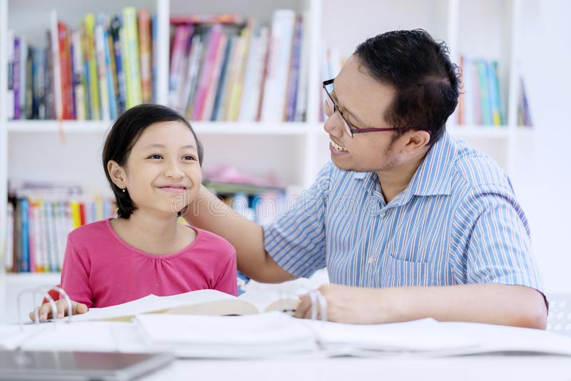 轻拍他的学生的头年轻老师 免版税库存图片