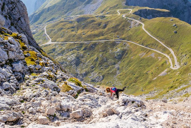轻松妇女摆在滑稽与她的腿,高在Mangart马鞍上的一个山行迹,有可看见下面Mangart的路的  库存照片
