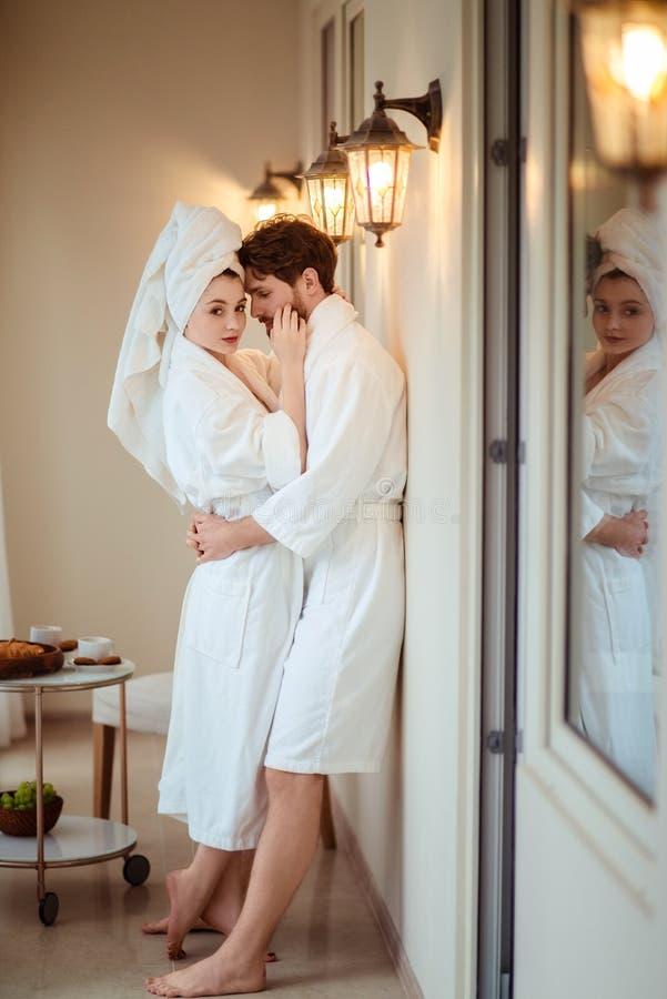 轻松年轻女性和男性在旅馆里穿白色浴巾,互相拥抱,感觉安心在洗浴以后,立场 免版税库存图片