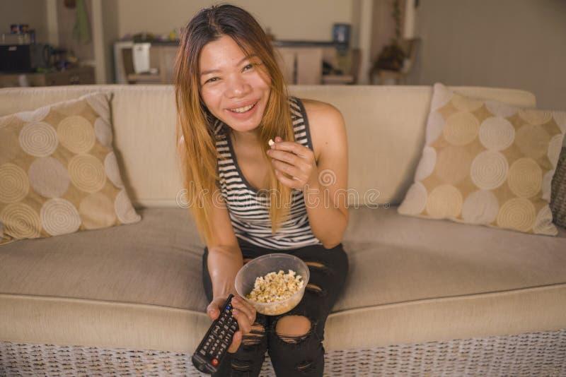 轻松的亚裔印度尼西亚妇女观看的电视喜剧电影或滑稽的系列情节笑快乐在客厅沙发 库存照片