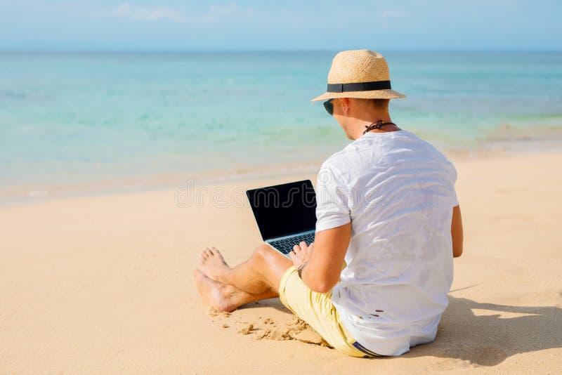 轻松的人与在海滩的膝上型计算机一起使用 库存图片