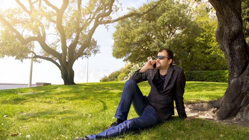 轻松的企业人坐绿草在树附近,谈话在智能手机 免版税图库摄影