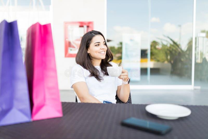 轻松的在购物以后的妇女饮用的咖啡 免版税库存图片
