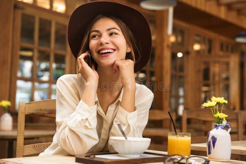 轻松的妇女佩带的帽子画象发表演讲关于智能手机 免版税库存图片