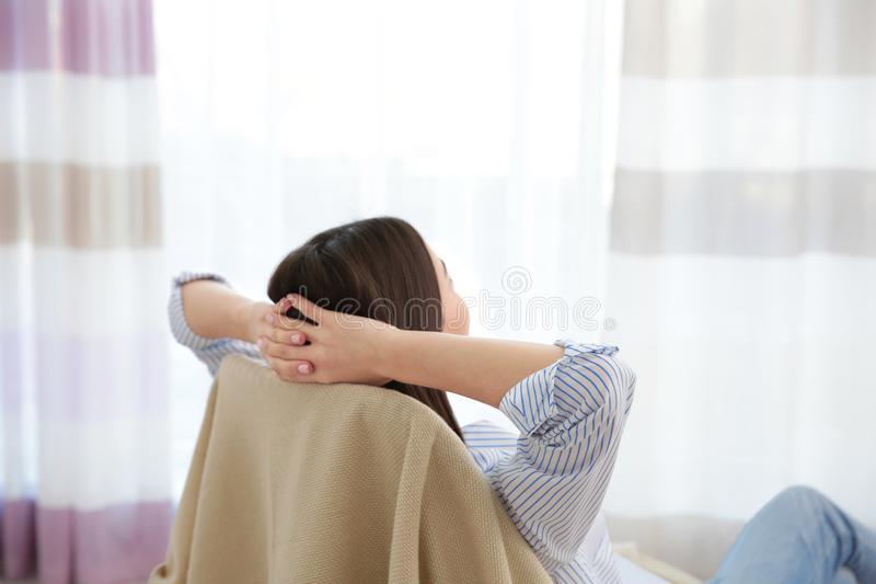 轻松的妇女背面图用在她的头后的手 库存照片