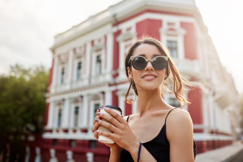 轻松的年轻可爱的妇女画象有黑发的在看黑的成套装备的尾巴发型,等待 免版税库存照片