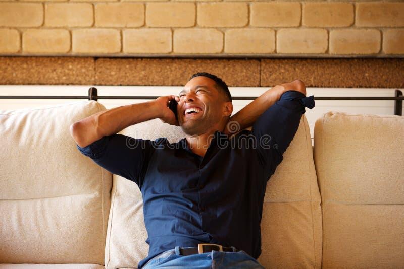 轻松的年轻黑人谈话在手机用在他的头后的手 图库摄影