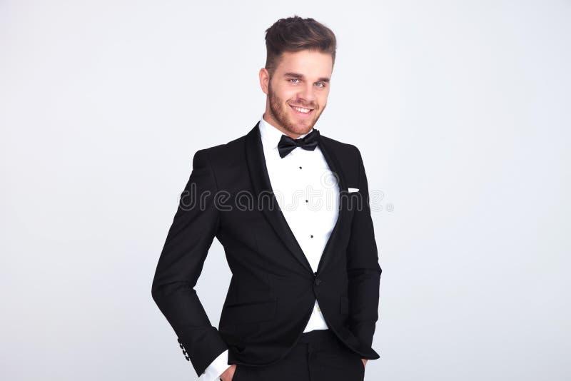 轻松的微笑的绅士画象黑无尾礼服身分的 免版税库存照片