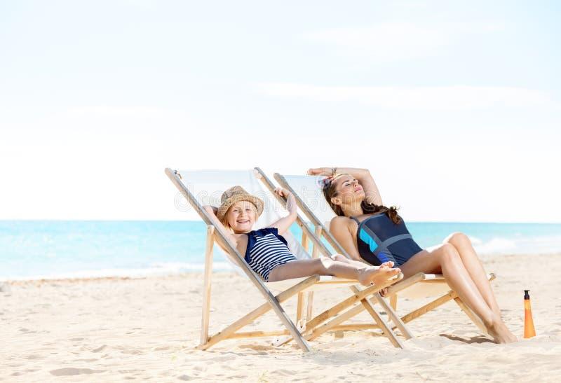 轻松的母亲和孩子海滩的坐海滩睡椅 免版税库存图片