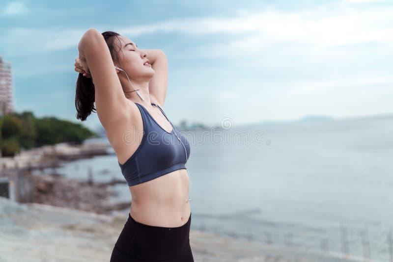 轻松的运动员亚洲人跑步的妇女健身锻炼室外在海滩 免版税库存照片