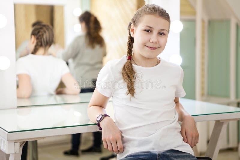 轻松的青少年的女孩坐在化装室在熔铸以后,母亲的模型准备好离开演播室 库存照片