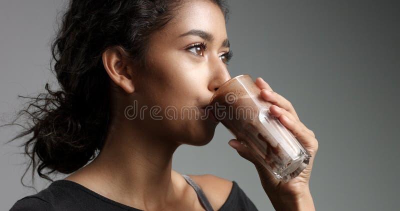 轻松的黑顶面饮用的mocca的,热巧克力,从一块高玻璃的caffee笑的可爱的中东女孩 免版税库存图片