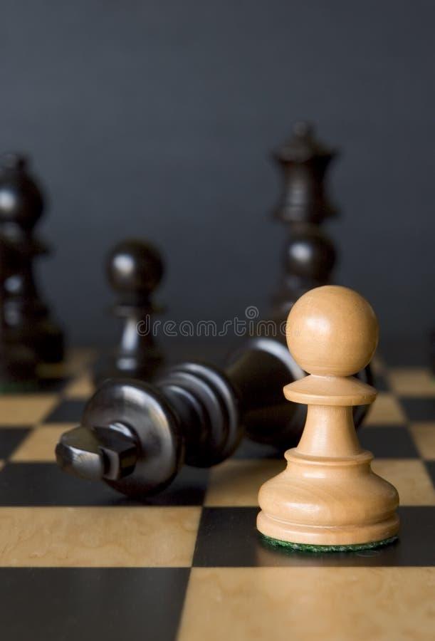 轻的典当击败黑暗的女王棋子 库存照片