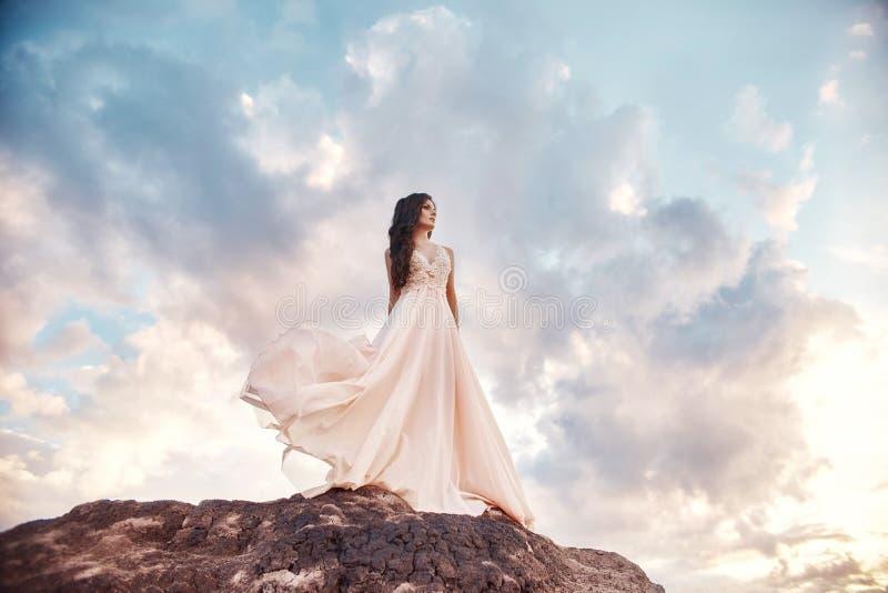轻的夏天礼服灰棕色的美丽的女孩在山走 轻的礼服在风,蓝色夏天天空振翼 美妙 免版税库存照片
