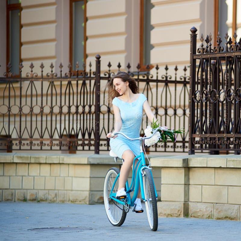 轻的女孩骑有牡丹的葡萄酒自行车在手上 图库摄影