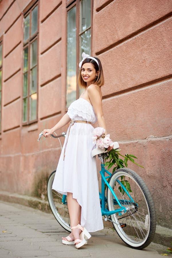 轻的女性在有花束牡丹的减速火箭的自行车倾斜 免版税图库摄影