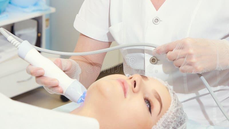 轻的红外疗法 整容术头做法 秀丽妇女面孔 化妆沙龙设备 脸皮回复 库存照片