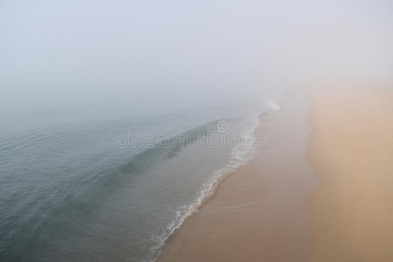 轻的绿松石海浪消失入沿光滑的桑迪岸的雾 库存图片