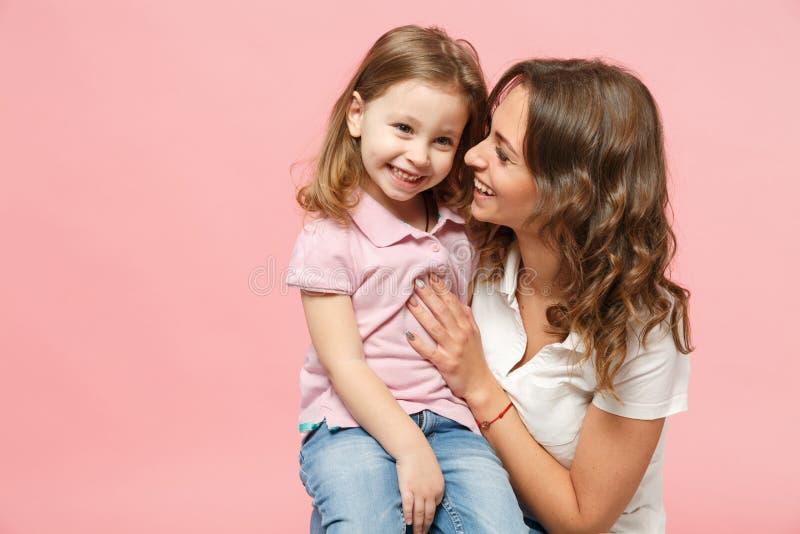 轻的衣裳的妇女获得与逗人喜爱的儿童女婴的乐趣 母亲,在粉红彩笔墙壁上隔绝的小孩女儿 免版税库存图片