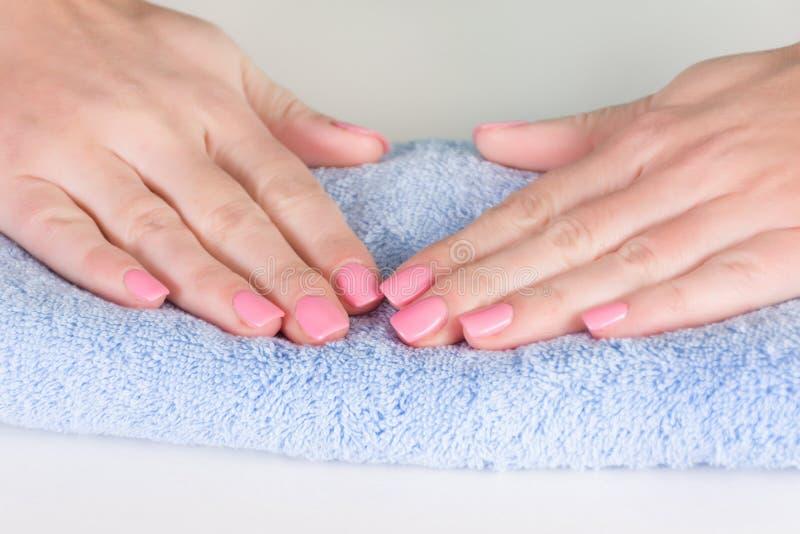 轻轻地在女孩手指钉子的桃红色修指甲在蓝色毛巾 免版税图库摄影