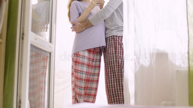 轻轻地拥抱他怀孕的妻子的爱恋的丈夫 预期婴孩的诞生的愉快的家庭 库存照片