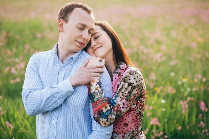 轻轻地拥抱和亲吻在阳光下的美好的年轻夫妇在有桃红色花的新鲜的春天草甸 愉快的时髦的家庭 免版税库存照片