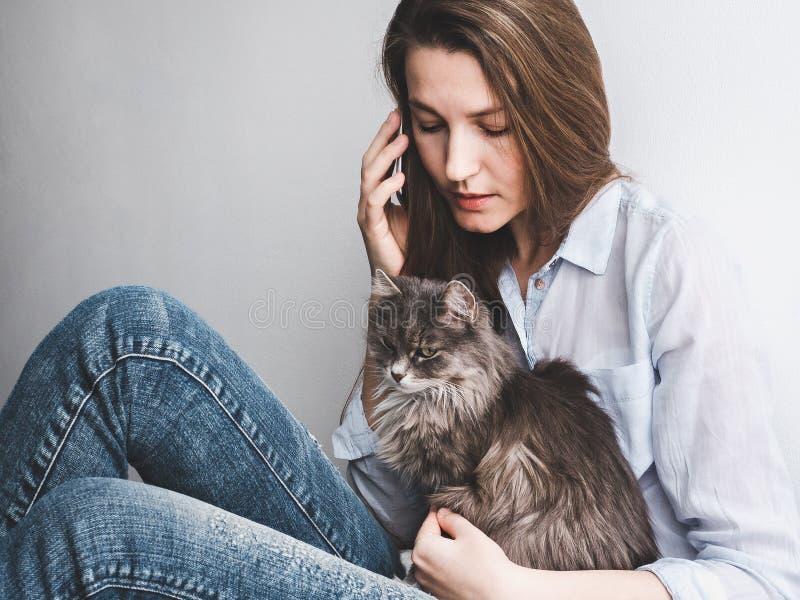 轻轻地拿着小猫的少妇 免版税图库摄影