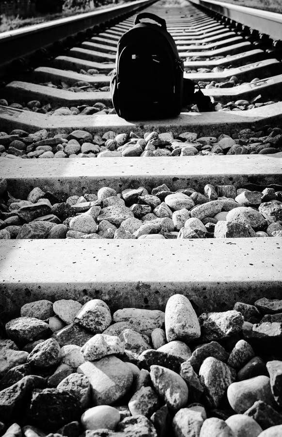 轻量级远足的黑背包,单独站立在铁路轨道 银色被镀的照片 图库摄影