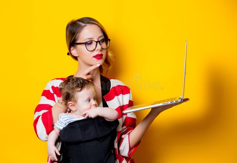 载体和母亲的小婴孩有膝上型计算机的 库存图片