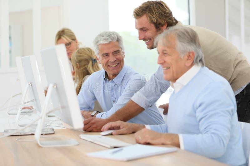 辅导员帮助的前辈在信息学方面 免版税库存图片