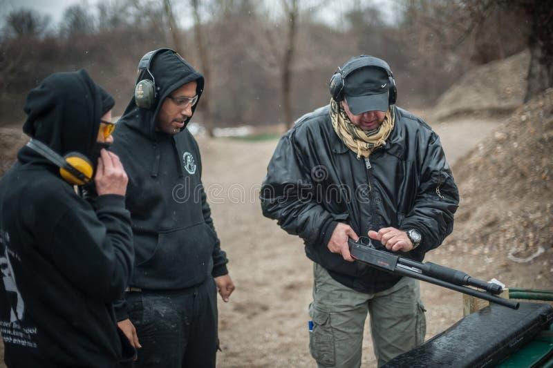 辅导员泽利科武伊契奇教如何安全使用泵浦猎枪 免版税库存图片