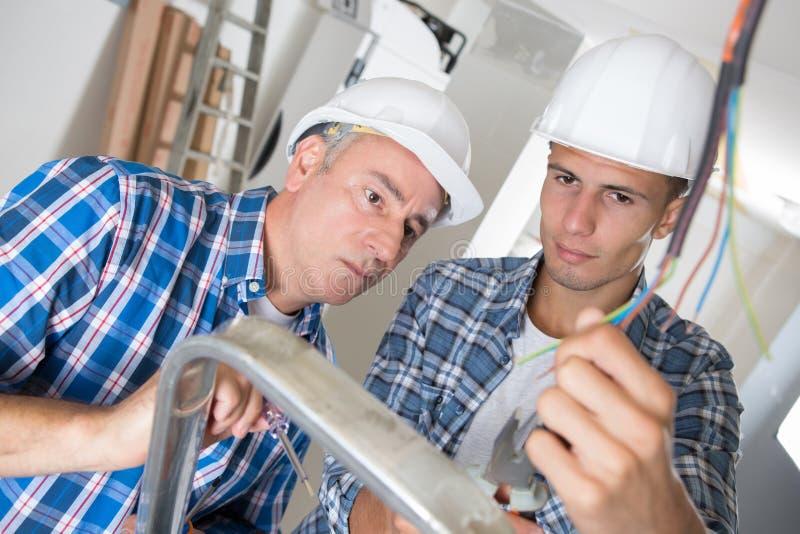 辅导监督的男性电机工程师 免版税图库摄影