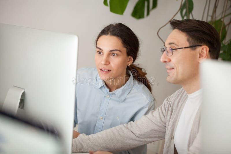 辅导者帮助的实习生解释的实习生或新的雇员在网上 免版税库存照片