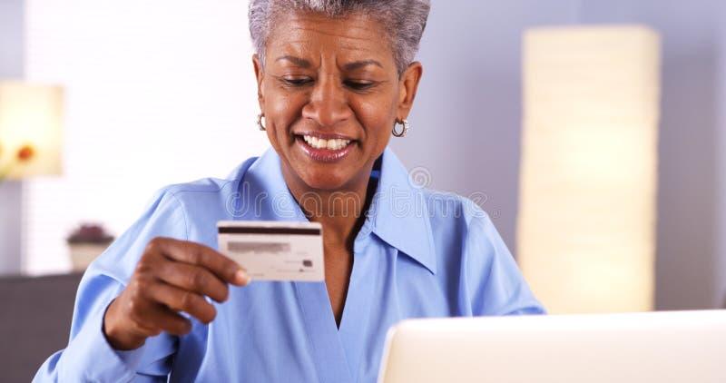 输入卡片信息的愉快的成熟黑人妇女 库存照片
