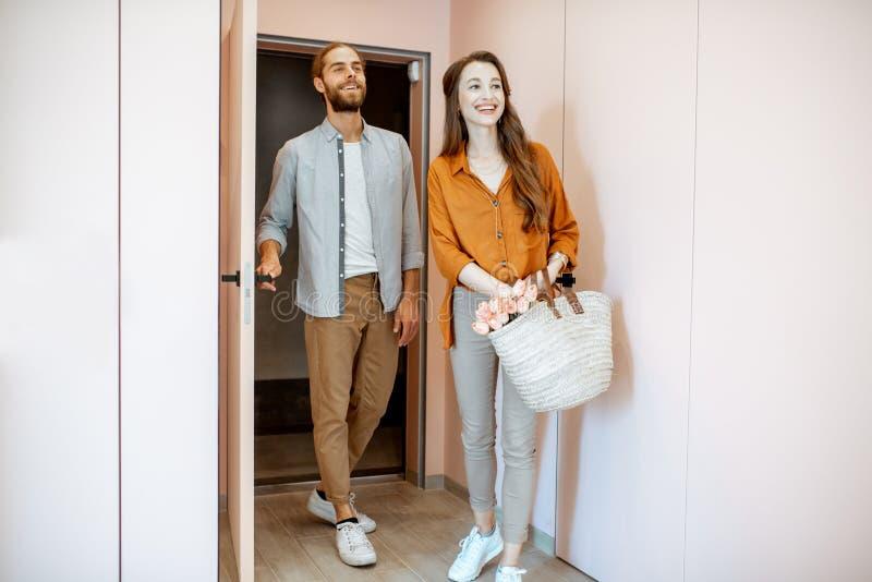 输入在家在现代舱内甲板的走廊的年轻夫妇 库存图片