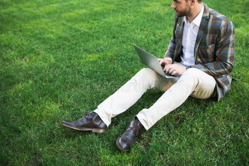 输入在草的膝上型计算机的沉思商人 免版税库存图片
