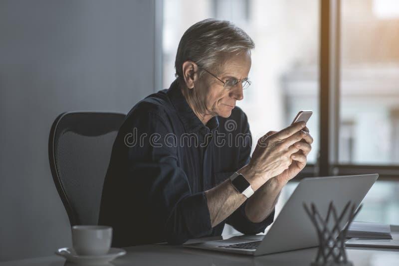 输入手机的严肃的老商人 库存图片
