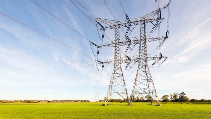输电线和定向塔双重行在平的荷兰农村土地 免版税库存照片