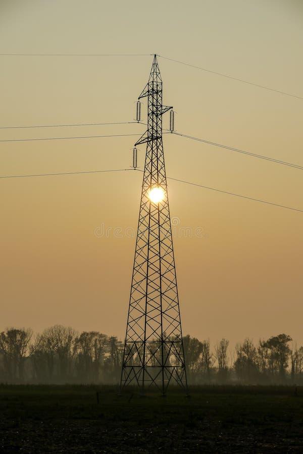输电线和电定向塔在日落,数字照片图片作为背景 免版税库存照片