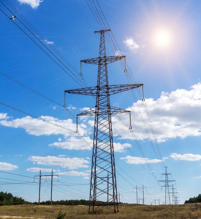输电线和电线,在日落的云彩塔  免版税库存照片